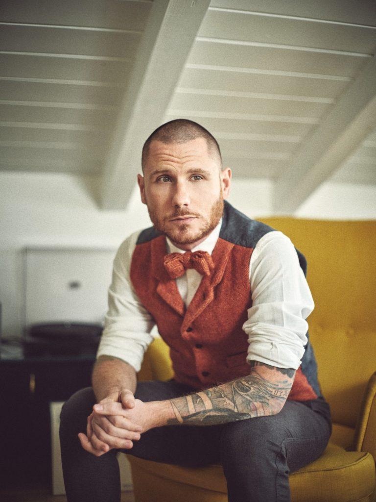 sposo a casa su poltrona vintage. hypster groom con tattoo servizio fotografico