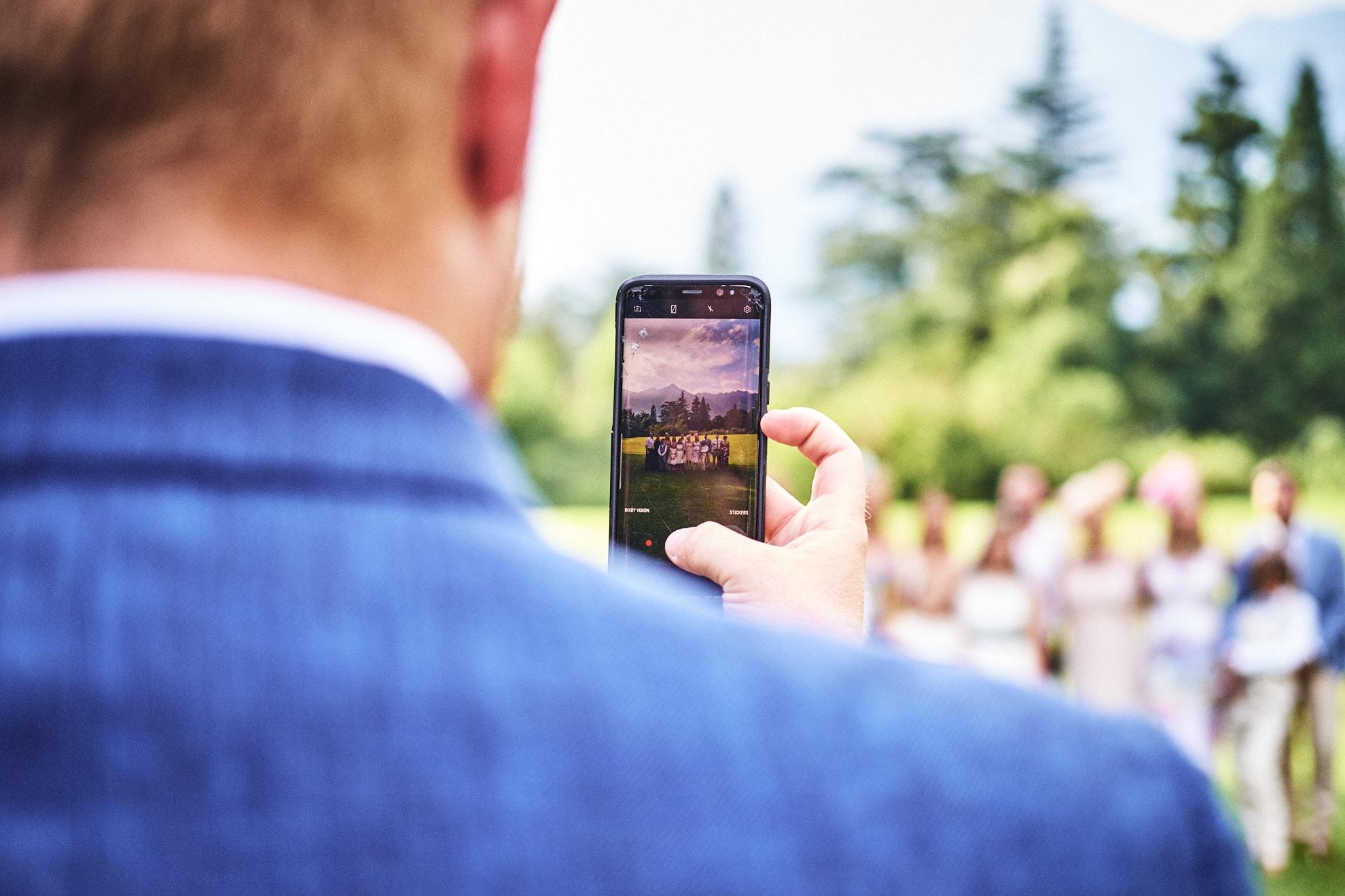 invitato al matrimonio di spalle scatta una foto di gruppo agli sposi e amici