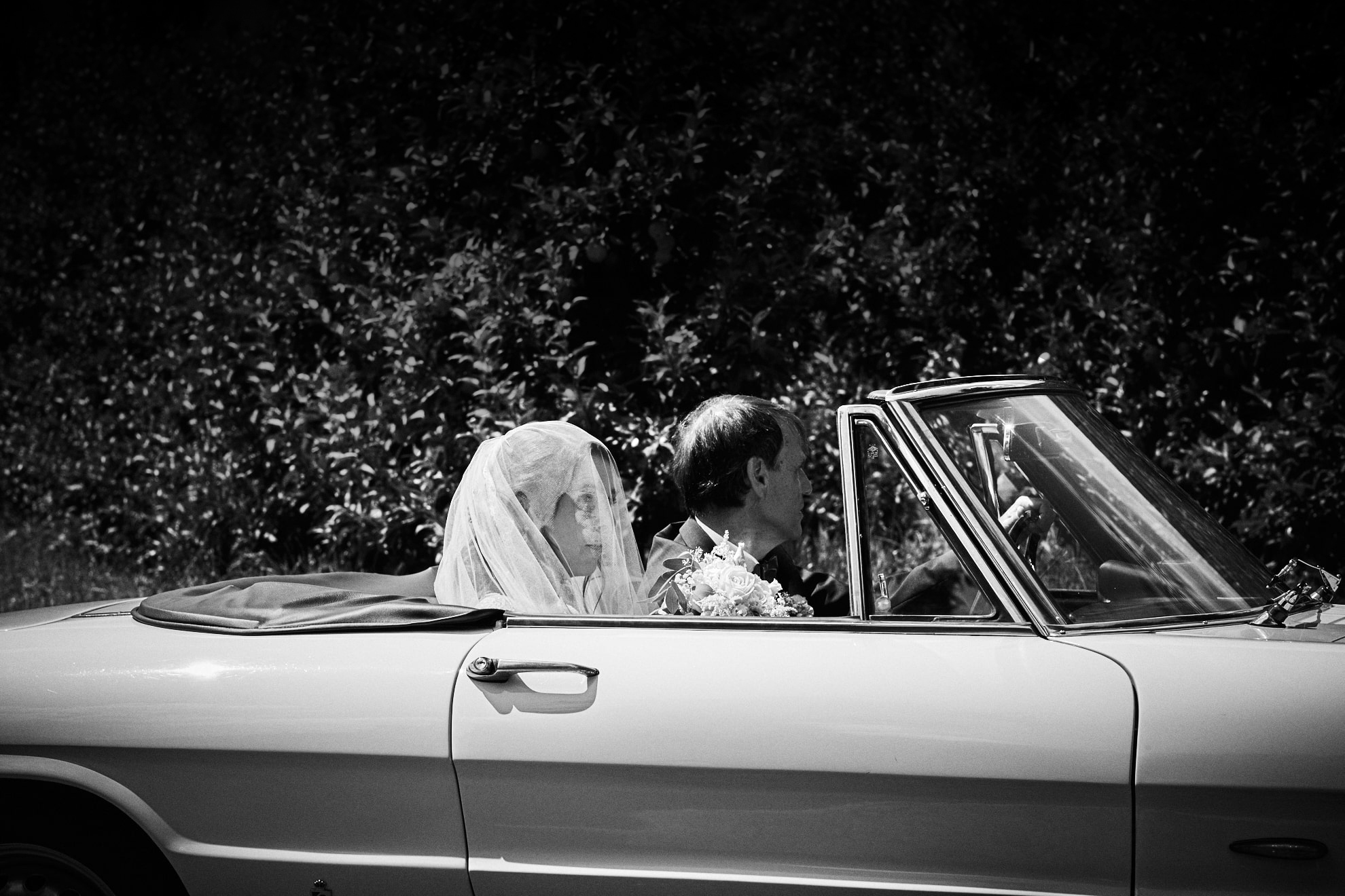 bride is coming. black and white picture. Bride with her dad in vintage car.