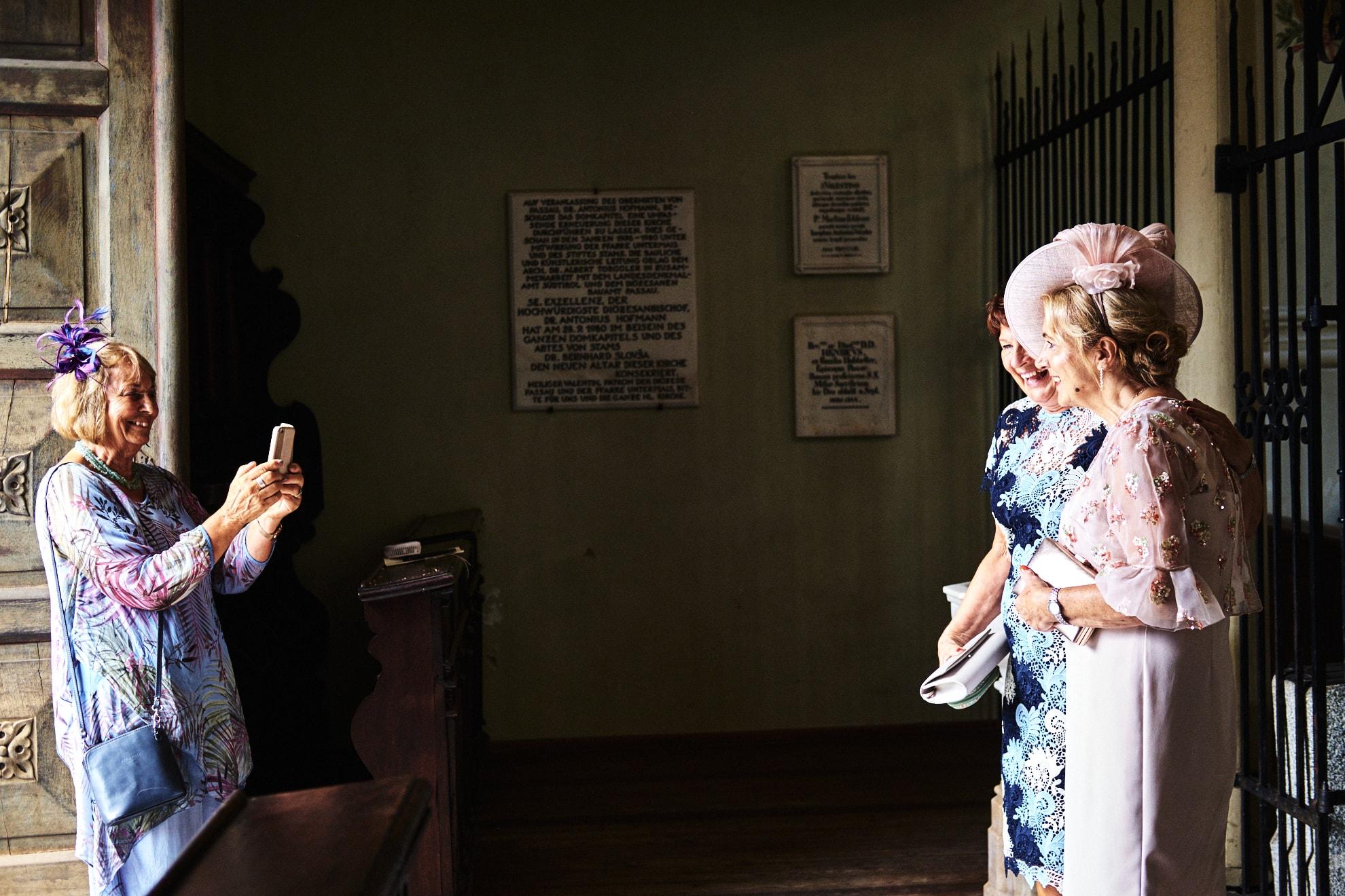 zie dello sposo invitate al matrimonio si scattano una fotografia con il cellulare all'ingresso della chiesa prima della celebrazione delle nozze