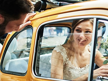 bride inside the old yellow car. groom is opening the door reportage photo shoot